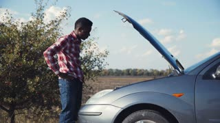 4K Young stylish african guy having automobile problems and stranded roadside checks under the hood of his car