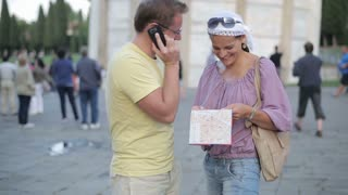 Man talks on cellphone, woman looks at map