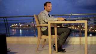 Businessman works in the evening from terrace