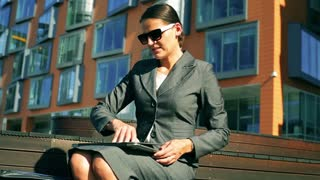 Businesswoman working on laptop, talking on cellphone