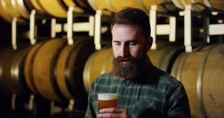 a brewmaster expert checks the quality of the freshly tapped beer from wooden barrels formerly used for flavour the wine or beer.