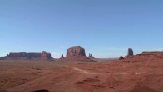 A Cowboy On His Horse Rides To A Vista Of Monument Valley