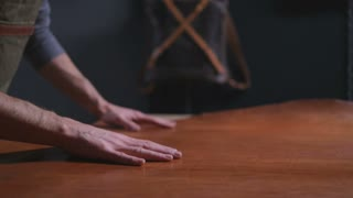 A craftsman touching a big piece of leather on the table slow motion