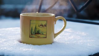 a cup with hot tea on a snow-covered chair
