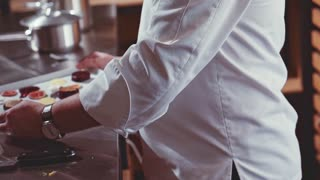 A delicious gourmet meal is being presented by the chef in a restaurant kitchen, ready for service to the customer. Slow Motion. Close-up of chef hands cooking and preparing food.