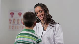 A female doctor with a child taking his heart rate