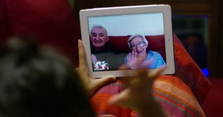 A girl from the couch of her home greets you with its tablet in video call her grandparents who loves and has not seen for so long, greets them with her hand and blows a kiss and they smile because they are happy and miss their granddaughter
