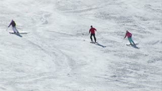 A Group Of Three Skiiers Turn In Formation