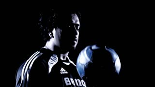 A Latino man juggles a soccer ball against a black background.