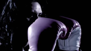 A Latino woman boxes against a black background.