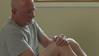 A main rubs his injured knee to sooth pain