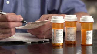 A man looks over his medical prescriptions, close up