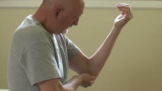 A man rubs and puts ice on his injured elbow to sooth pain