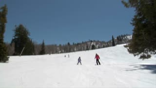 A Mom Leads Her Duaghter Down A Gentle Ski Hill