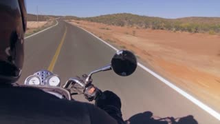 A motorcycle rider in a lonely desert road