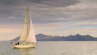 A Sailboat Glides On Calm Water Near Mountains