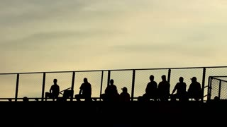 A silhouetted group of people watching from the stands