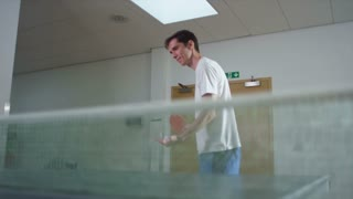A young man plays table tennis indoors, shot on RED EPIC
