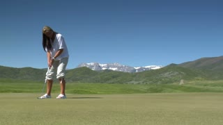 A Young Woman Putts On Golf Green With Snowy Mountains In Distance