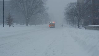 Ambulance driving down snow covered street during winter blizzard