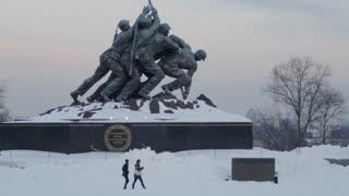 Couple Walking in Front of Iwo Jima Marine Corps War Memorial in Winter