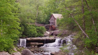Old mill with water wheel in lush green summer forest