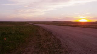 Car driving down dirt road at sunset in Badlands National Park