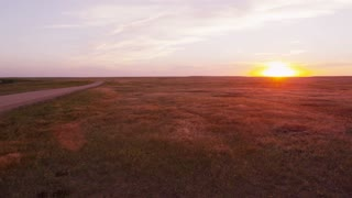Pan across grasslands at sunset with female photographer
