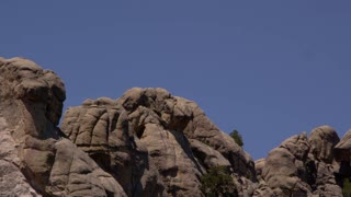 Pan left onto close shot of Mount Rushmore faces