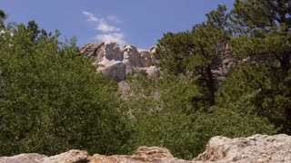 Mount Rushmore slider shot let through granite and trees onto Mt. Rushmore