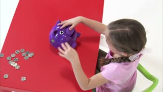 Above Shot of Eight Year Old Girl Putting Money in Piggy Bank