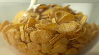Adding some milk to corn flakes in glass bowl super slow motion shot