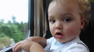 Adorable baby traveling by train. Baby next to train window. Toddler touching and pointing to camera lens