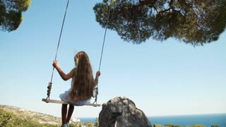 Adorable girl on a swing. Happy child looking at camera