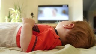Adorable toddler baby boy watching TV