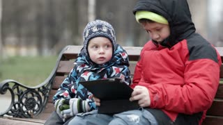 Adorable young boy watching his brother as the two sit together on a wooden park bench in warm winter clothing with the older child using a tablet computer