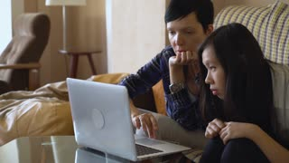 Adult caucasian woman looking at laptop explain something young asian girl. Multicultural team work with computer indoors. Vietnamese girl focus on screen. Older female shows errors that must be