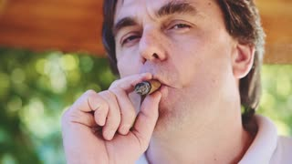 Adult Man is smoking cigar outdoors in the garden. Slow Motion 240 fps. Man is resting in a park during summer afternoon. Smoke in Slow Motion.