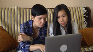 Adult woman with short hair explain main points and showing on screen computer. Asian young female listening and ask questions. Two casual women in the creative office or startup company working