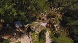 AERIAL: Amazingly beautiful waterfall falling on big rocks splashing around