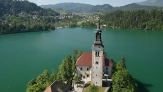 AERIAL: Beautiful small church on island Bled in natural lake