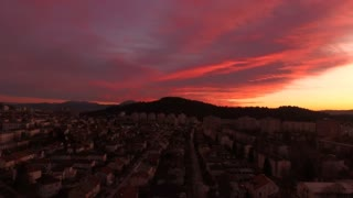 AERIAL: Big busy city at amazing reddish sunset