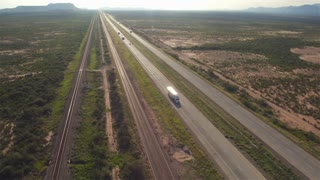 AERIAL: Cars and transportation semi trucks driving on busy highway