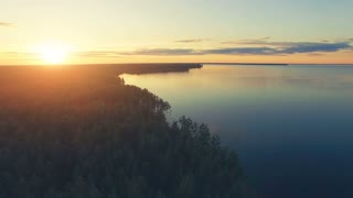 Aerial Drone Flight Footage: Back Flight above calm Water and forest in sunset soft light. Magestic landscape. Kiev Sea, Ukraine, Europe. 4K resolution