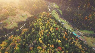 Aerial Drone Footage View: Flight over autumn mountain village with forests, fields and river in sunrise soft light. Carpathian Mountains, Ukraine, Europe. Majestic landscape. Beauty world. 4K