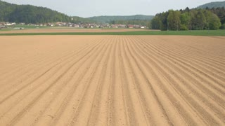 AERIAL: Empty plowed soil lines on agrarian field prepared for crop planting