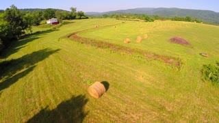 Aerial farm flyover summer haybails