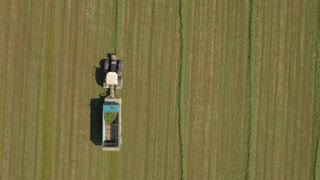 AERIAL: Farmers in tractors working on farm field collecting hay fodder in wagon