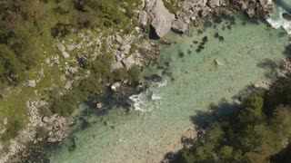 AERIAL: Fast green river and whitewater rapids running in rocky riverbed