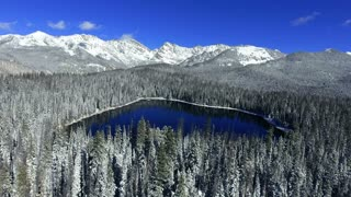Aerial flight over a wintry snow covered lake in the Colorado Rocky Mountains in winter